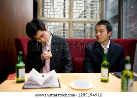 Young businessman lighting a cigarette while sitting with a colleague inside a living room.