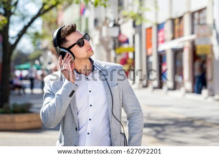 young businessman listening to music outdoor #627092201