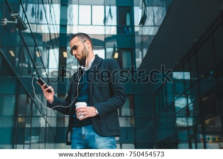 Young businessman listening to the music on a coffee break #750454573