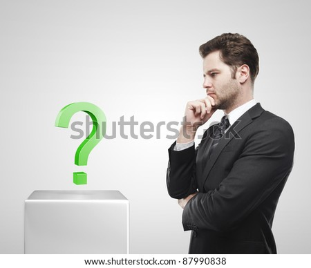 Young  businessman look at the green question mark on a white pedestal. On a gray background