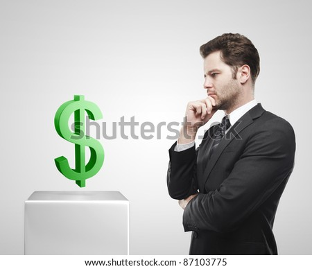 Young  businessman look at the green US dollar sign on a white pedestal. On a gray background