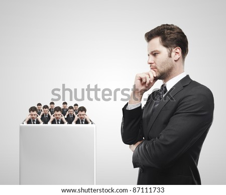 Young  businessman look at the group of businessmen on a white pedestal.Thinking men representing a social network. Conceptual image of a open minded men.On a gray background
