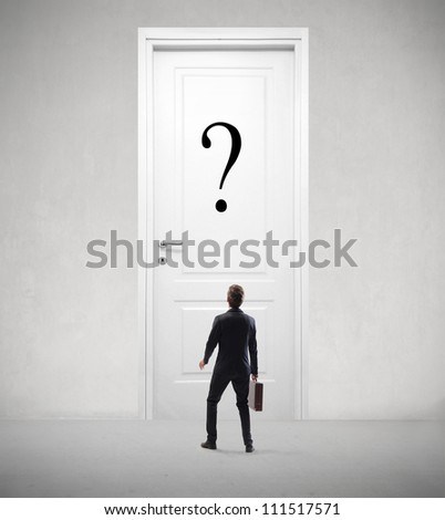 Young businessman looking at a door with a question mark on it