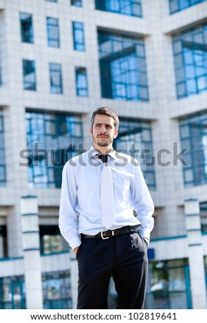 Young  businessman looking at camera with confidence against his office building