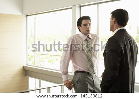 Young businessman looking at male colleague while standing by railing in office