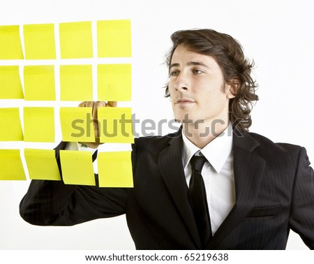 young businessman looking at postit reminder notes