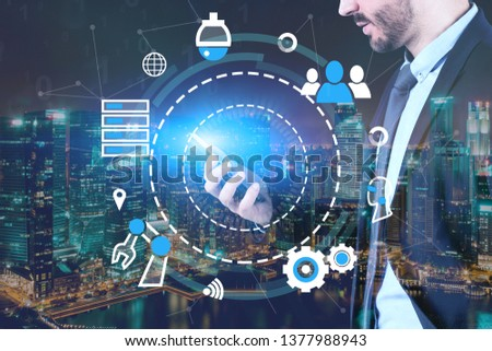 Young businessman looking at smartphone over night city background with double exposure of GUI with internet icons. Concept of hi tech in business #1377988943