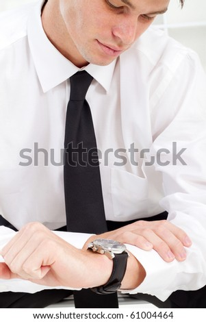 young businessman looking at watch