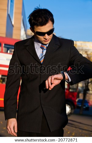 Young businessman looking at wristwatch outdoors
