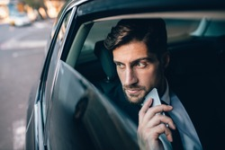 Young businessman looking away while sitting on the back seat of a car. Business executive thinking and looking outside window of taxi.