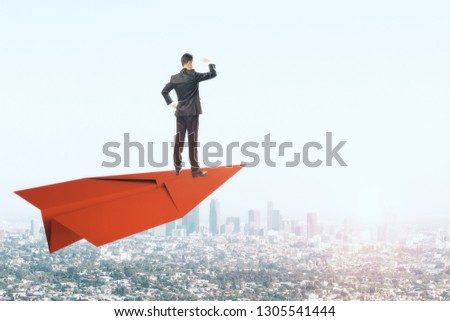 Young businessman looking into the distance while standing on red paper plane. Sky and city background. Freedom and vision concept #1305541444