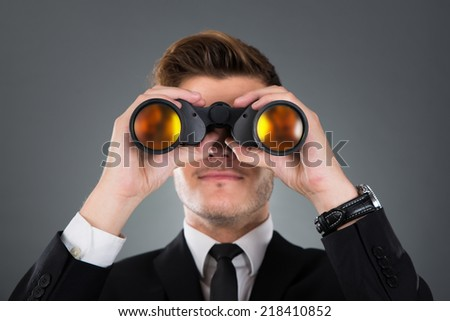Young businessman looking through binoculars against gray background #218410852