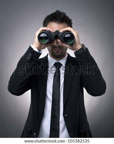 Young businessman looking through binoculars - market research concept
