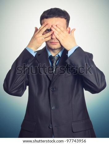 Young businessman looking through his fingers on dark background