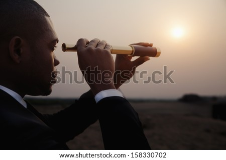 Young Businessman Looking Through Telescope In The The Desert