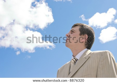 Young businessman looks upwards on a background of the blue sky