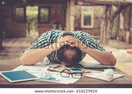 Young businessman lying face down on the desk., Business Failure concept