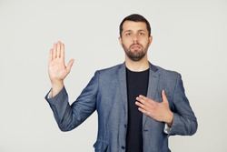 Young businessman man with a beard in a jacket, swears, putting his hand on his chest and open palm, making an oath of promise of loyalty. Portrait of a man on a gray background.