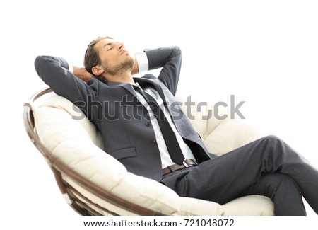young businessman meditating in big comfortable armchair #721048072