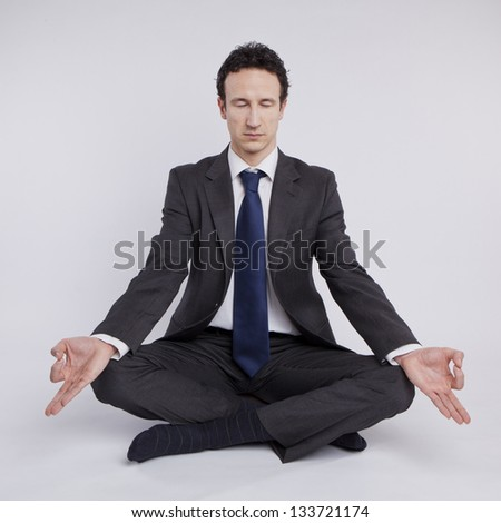 young businessman meditating in yoga lotus pose on white background