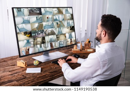 Young Businessman Monitoring CCTV Camera Footage On Computer Over Wooden Desk #1149190538