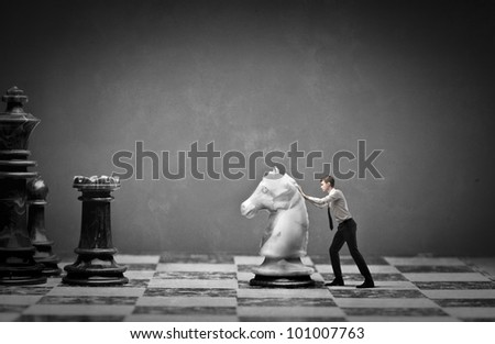 Young businessman moving a knight on a chessboard