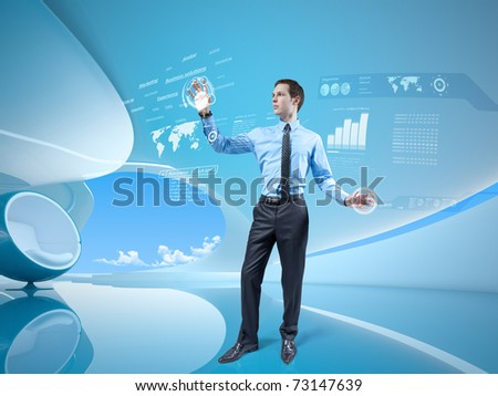 Young businessman navigating holographic virtual reality interface in stylish interior. Future collection. One of a series.