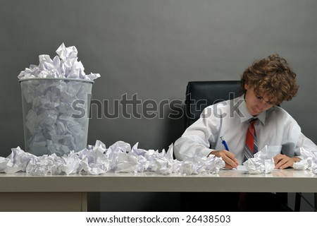 Young businessman next to stack of crumpled paper
