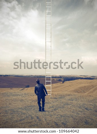 Young businessman observing a high ladder on a green meadow - stock photo