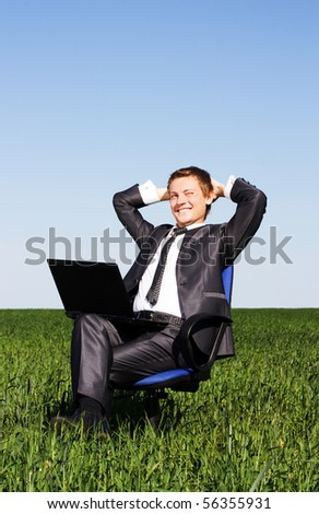 Young businessman on a green field