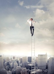 Young businessman  on a ladder over a big city looking ahead