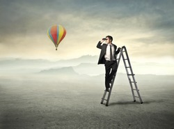 Young businessman on a ladder using binoculars and hot-air balloon in the background
