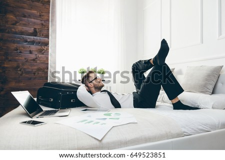 Young businessman on bed working with a laptop from his hotel room #649523851