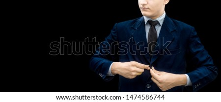 Young businessman or groom fasten button or buttoning of his dark blue colored jacket or blazer jacket isolated on black with a black colored necktie. Making a perfect business look. #1474586744