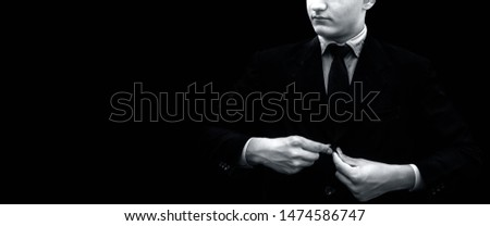 Young businessman or groom fasten button or buttoning of his dark blue colored jacket or blazer jacket isolated on black with a black colored necktie. Making a perfect business look. #1474586747