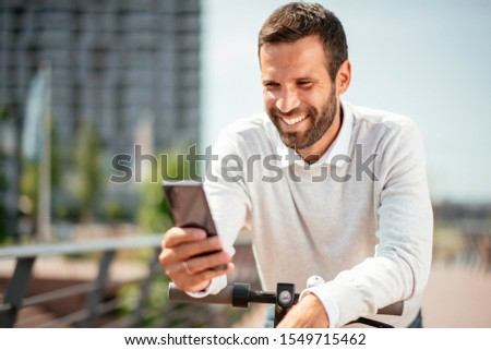 Young businessman outdoors. Handsome businessman using phone on his electric scooter stock photo