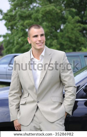 Young businessman outside of office with cars on background