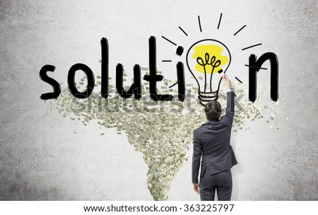 Young businessman painting a bright yellow bulb with a brush in the word 'solution' instead of the second 'o' on the white wall. Dollar tornado under it. Back view. Concept of finding a solution.