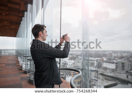 Young businessman photographing a city on the phone with a skyscraper.