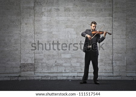 Young businessman playing the violin on a street
