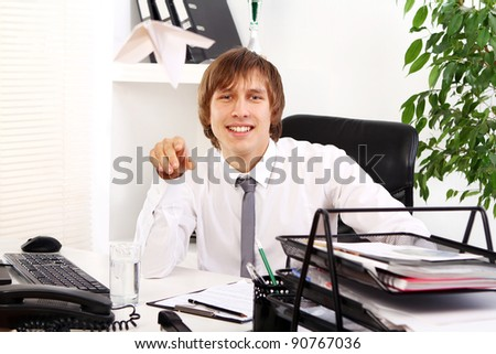 Young businessman playing with paper airplane in his office