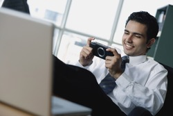 Young businessman playing with Playstation Portable