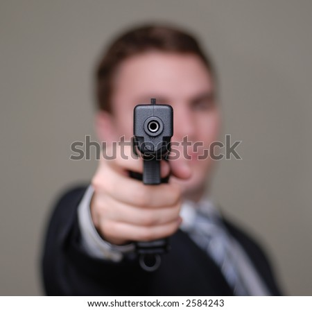 Young Businessman Pointing A Gun Towards The Camera ...