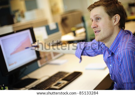 Young businessman pointing at graph on PC