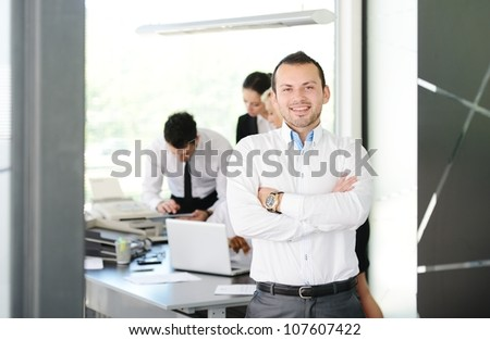Young businessman portrait and his colleagues working at the back
