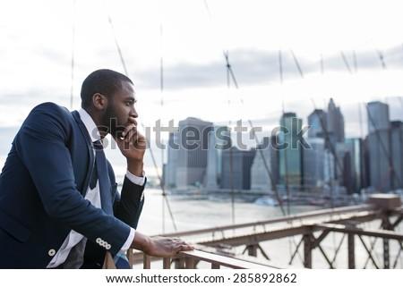 Young businessman portrait on Brooklyn Bridge. New York City.