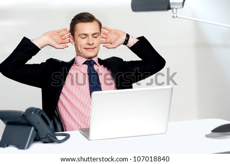 Young businessman posing in a relaxed manner with hands behind head looking at his laptop