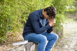 Young businessman praying outdoor garden