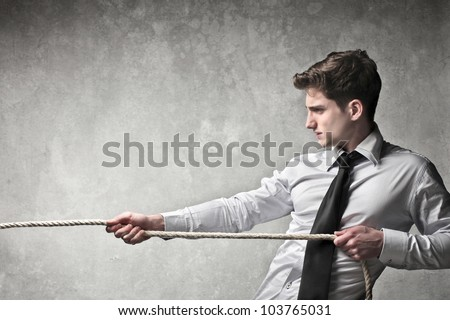Young businessman pulling a rope