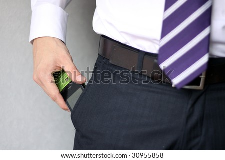 Young businessman pulling cellphone out of his pocket